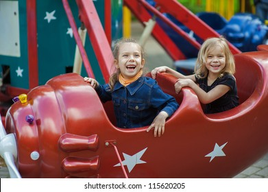 Two funny sisters on carousel ride in red airplane in children's park.