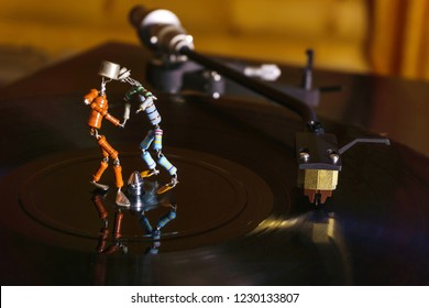 two funny small human figures, roughly welded together from resistors and transistors, dance on a rotating vinyl record in twilight; stylized as an vintage photo
