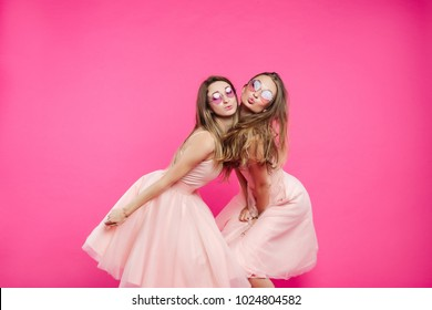Two funny and sweet girlfriends wearing in pink dresses, sunglasses like princes or candies, having fun and sending kiss at camera. Pretty women dancing, jumping, smiling. Fashion, shopping concept.