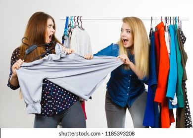 Two funny women arguing with each other during shopping about piece of clothing. Sales madness