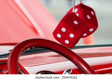 Two fuzzy dice hanging from the rear view mirror on a classic car.