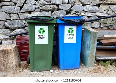 Two garbage bins in a row. One is for plastic and another one is for trash only. Recycling prevents pollution by reducing the need to collect new raw materials.  Reduce, Reuse, Recycle.
