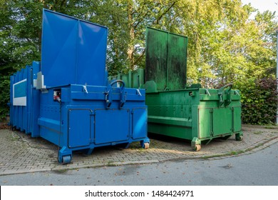 two garbage compactors Standing next to each other on the premises of a hospital