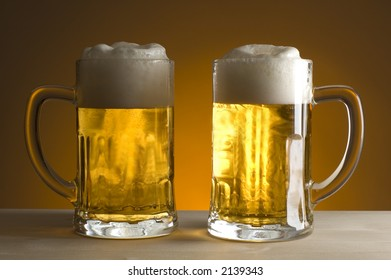 two gasses of beer on orange background close up