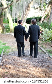 Two gay male grooms walking hand in hand down a garden path together.  Symbolizes the pathway of life.  Some motion blur on legs as they are actually walking.