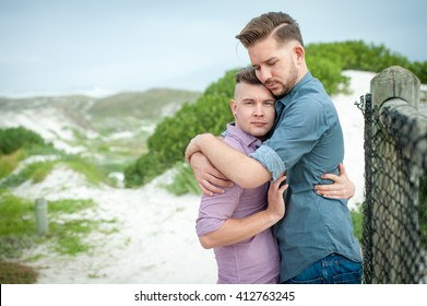 two gay men lovingly embrace and kiss next to a beach fence