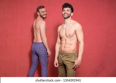 two gay men shirtless, one is in front, other one is in back. both smiling to camera.