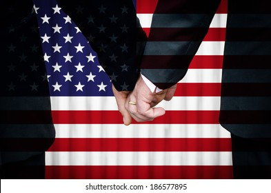 Two gay men stand hand in hand before a marriage altar overlaid with the flag of the United States of America, having just been married within a State that has legalized Same-Sex Marriage legislation.