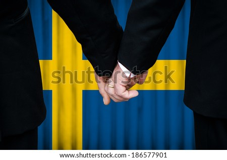 Two gay men stand hand in hand before a marriage altar featuring an overlay of the flag colors of Sweden, having just been legally married under the Same-Sex Marriage legislation of that country.