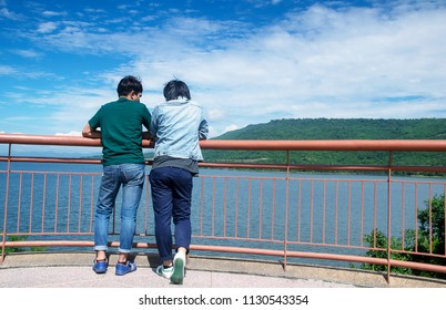 two gay men stand turn back on viewpoint Sky, mountains and rivers a romantic. lgbt, same-sex relationships and homosexual concept.
