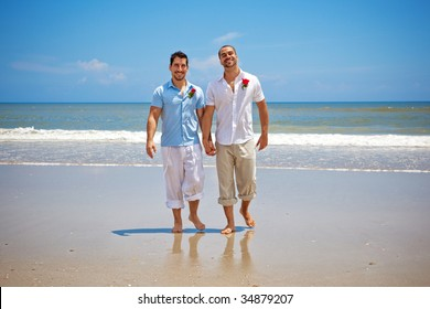 Two gay men walking on a beach after wedding ceremony