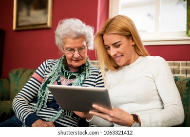 Two generation using tablet and smiling together, granddaughter learn grandmother how to use electronics