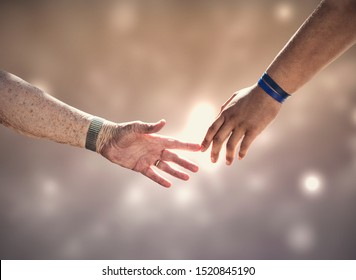 Two generations connecting. The hands of an old white woman and a young black man touching. Concept image about age, connections, diversity, race and cultures