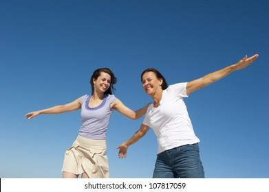 Two generations of women, mother and daughter, posing on a sunny day outdoor, with happy smiles and joyful, with clear blue sky as background and copy space.