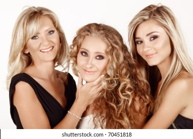 two generations of women: mother in her 40s with a beautiful teenage and young adult daughters with different hairstyles. Real life family.