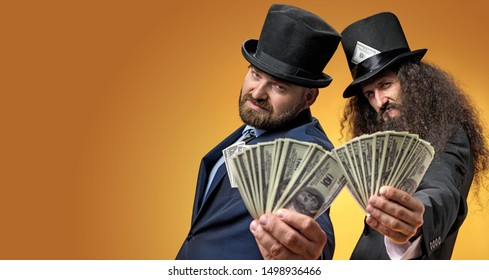 Two gentelmen holding dolars in their hands