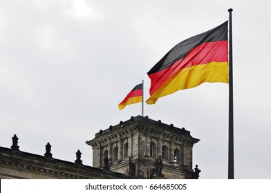 Two German flags on the background of the Reichstag in Berlin, Germany.