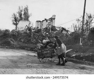 Two German women pushing their belongs in a cart past demolished buildings, Aachen, Germany. The battle of Aachen took place from October 2-21, 1944 and was the first major city occupied by Allies.