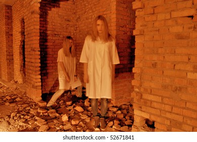 Two ghosts of  young girls in abandoned building ruins