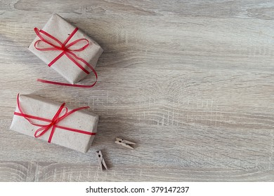 Two gift boxes with red ribbons, two clothespins on wood background with empty space for text. Top view with copy space