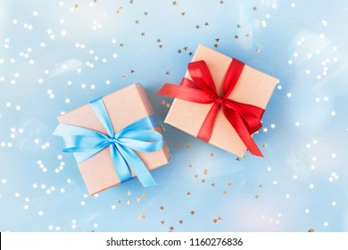 Two gift boxes wrapped in kraft paper and tied with ribbon on blue background decorated with confetti. Top view, gift idea for him and her.