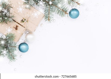 Two gift boxes wrapped kraft paper with Christmas decorations, spruce branches and Christmas balls on white background. Top view, holiday composition with snowy texture.