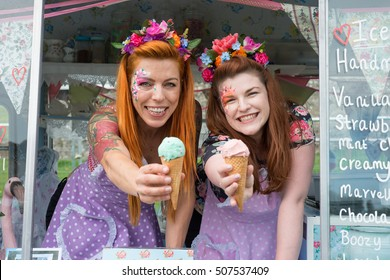 Two ginger haired ladies smiling wearing vintage spotted dresses holding ice cream out of truck