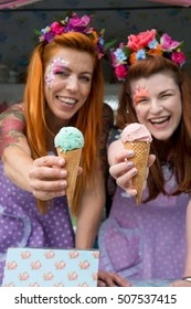 Two ginger haired ladies smiling wearing flower headbands and vintage spotted dresses holding ice cream out of truck. Portrait image with text space