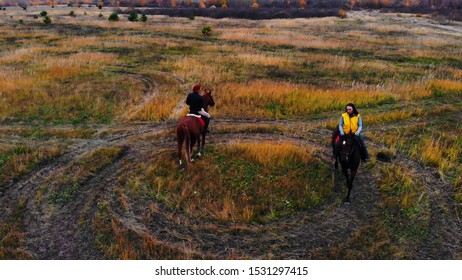 Two ginger horses with equestrians are going in circle on the field