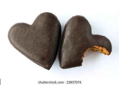 Two gingerbread hearts covered with chocolate with jam filling, one partially bitten.