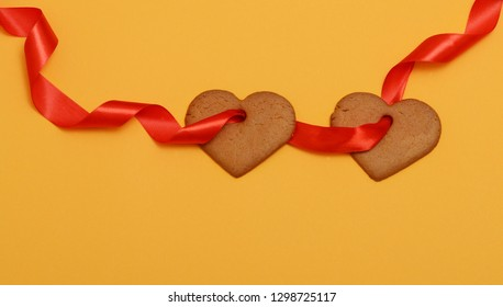 two gingerbread hearts strung on a red ribbon