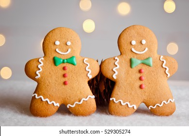 Two gingerbread man with candy standing on a blurred background. Christmas card
