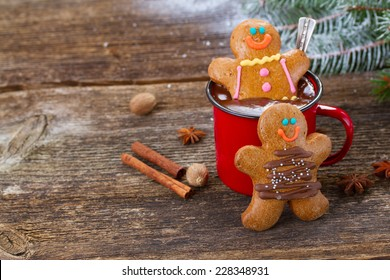 two  Gingerbread men with mug of hot chocolate on wooden table