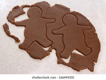 Two gingerbread men shapes cut into cookie dough
