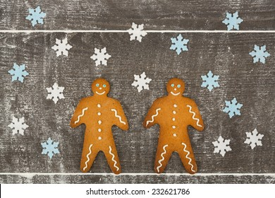 Two gingerbread men together on floury table with snowflakes and snowy environment from the flour on a dark wooden table.