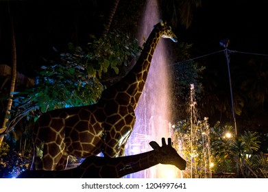 two giraffe statues at night with the fountain in the backside