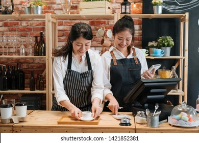 two girl barista and cashier in aprons standing and talking behind bar counter in cafe. waitress counting bills on calculator while holding notebook. smiling woman staff preparing coffee for customer