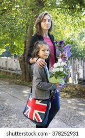 Two girl of different ages flowers on the street
