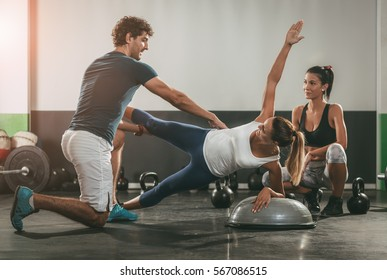 Two girl exercising at the gym with a personal trainer.