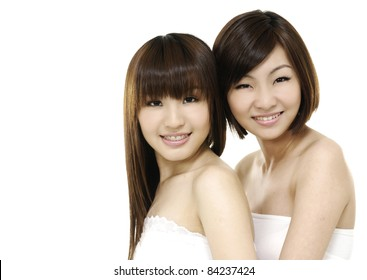 Two girl friends in bath dress together smiling