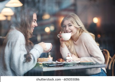 Two girl friends drinking coffee in the cafe