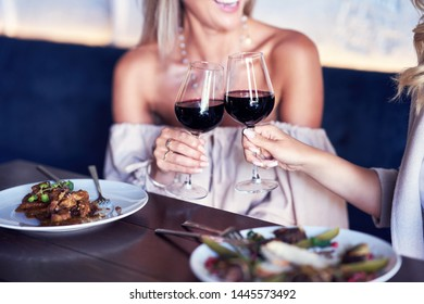 Two girl friends eating lunch in restaurant
