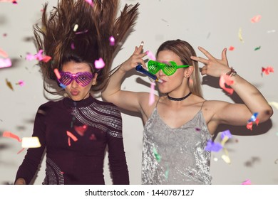 Two girl friends having fun, dancing and making crazy faces while taking photos at a party
