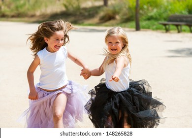Two girl friends running together holding hands in park.