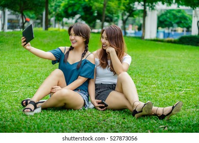 Two girl friends sitting on the grass taking a self portrait using a tablet computer