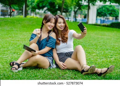 Two girl friends sitting on the grass taking a self portrait using a phone