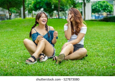 Two girl friends sitting on the grass having fun laughing