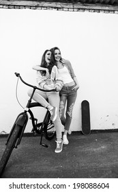 Two girl friends with skateboard and bicycle smiling. Outdoors, lifestyle.