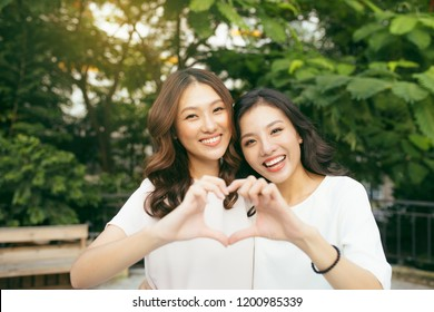 Two girl friends standing in a hug and forming heart shape with hands in the nature. Friendship concept