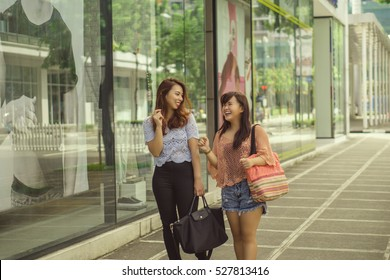 Two girl friends talking and walking on the sidewalk store